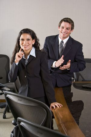 Young businessman applauding Hispanic female colleague in boardroom photo