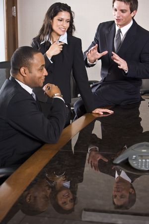 African American businessman with younger Hispanic businesswoman and male colleague Stock Photo