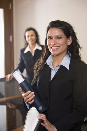 Hispanic businesswoman standing in boardroom with collleague in background photo