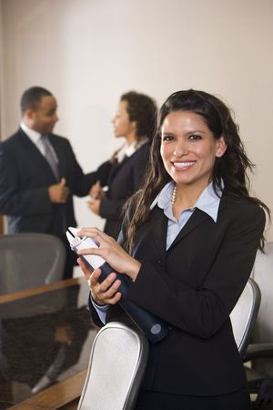 Hispanic businesswoman standing in boardroom, colleagues in background photo