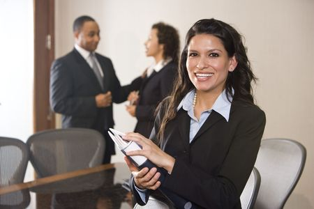 Hispanic businesswoman standing in boardroom, colleagues in background Stock Photo