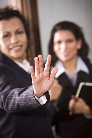 Two hispanic businesswomen, one gesturing with hand to stop photo