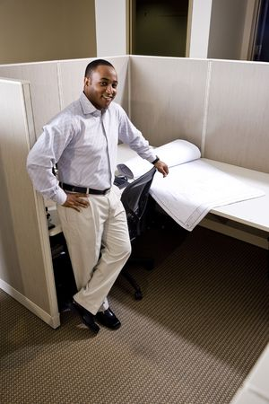 African American office worker standing in cubicle with floorplans photo