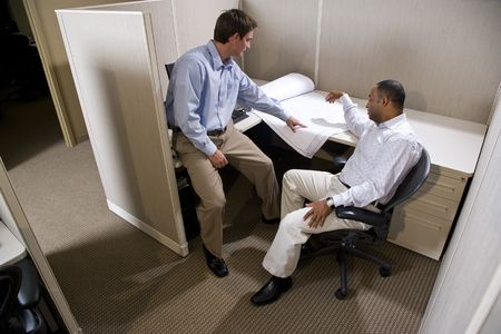 serious meeting: Two male colleagues working in cubicle with blueprints