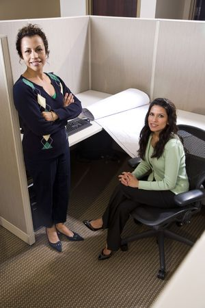 Two hispanic businesswomen meeting in cubicle working with blueprint Stock Photo - 6375536