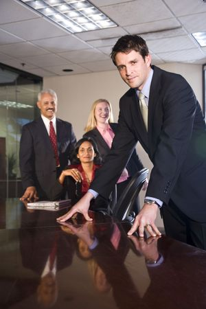 Businessman meeting in boardroom with multiethnic colleagues photo