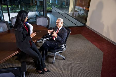 African American businessman and female colleague having discussion in boardroom