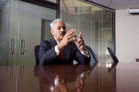 Serious African American businessman sitting at a boardroom table photo
