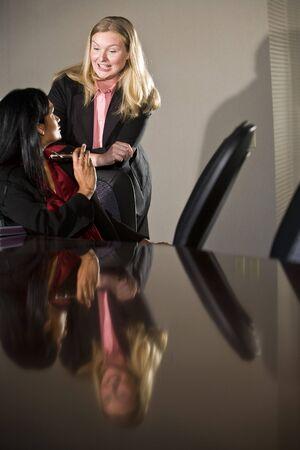 conversing: Two multi-ethnic businesswomen conversing in boardroom Stock Photo