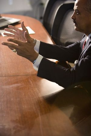 Mature African American businessman sitting at conference table conversing Stock Photo