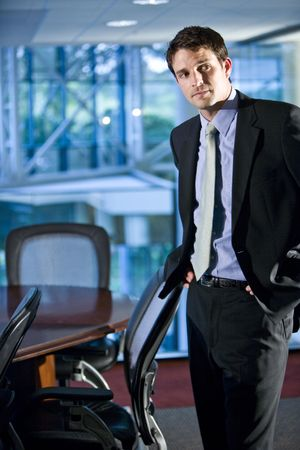 Young businessman standing in boardroom photo