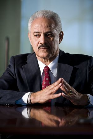 Mature African American businessman sitting at conference table photo