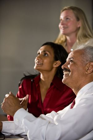 Three happy multi-ethnic businesspeople watching together photo
