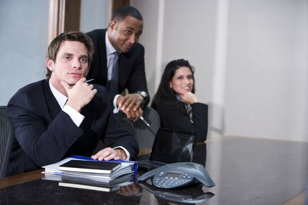 Serious young businessman with African American and Hispanic colleagues in background photo