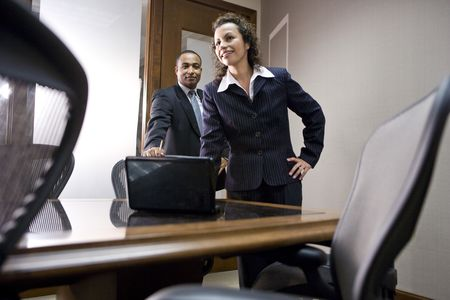 Hispanic businesswoman and African American businessman meeting in conference room photo