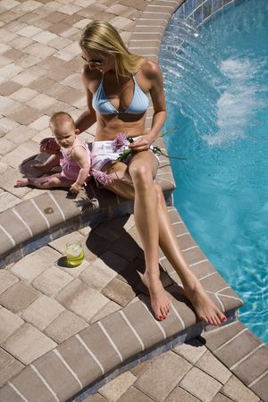 six month old: Mother and six month old baby playing by swimming pool
