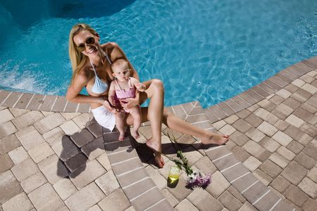 poolside: Mother and six month old baby playing by swimming pool