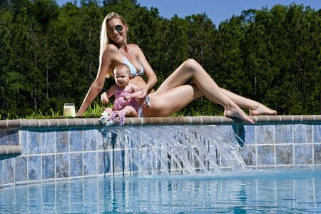 legs around: Mother and six month old baby playing by swimming pool