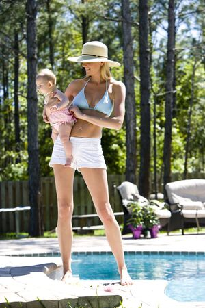 Mother carrying six month old baby next to a swimming pool Stockfoto
