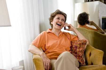 Senior woman in her 70s relaxing at home chatting on mobile phone photo
