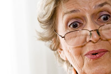 Close-up of elderly woman wearing reading glasses photo