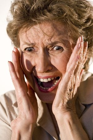 fear: Senior woman in her 70s with frightened look on her face Stock Photo