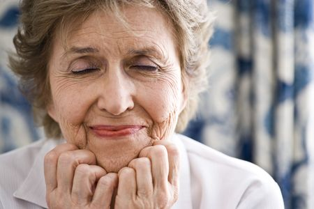 smile close up: Closeup of senior woman in her 70s with her eyes closed thinking happy thoughts Stock Photo