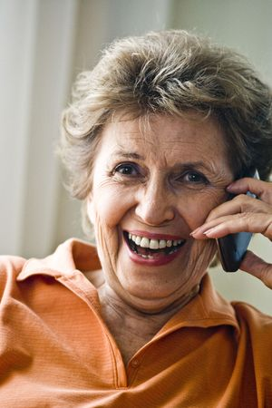 Close up of happy senior woman in her 70s on mobile phone photo