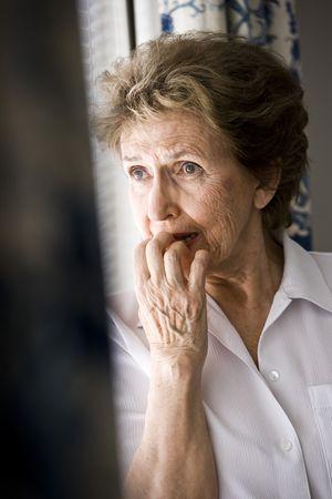 femme inqui�te: Triste femme senior dans sa fen�tre donnant des ann�es 70  Banque d'images