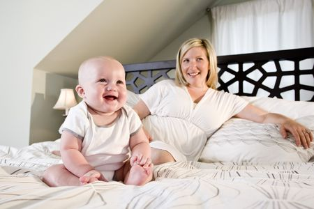 Happy 7 month old baby sitting on bed with mother Stock Photo - 6610543