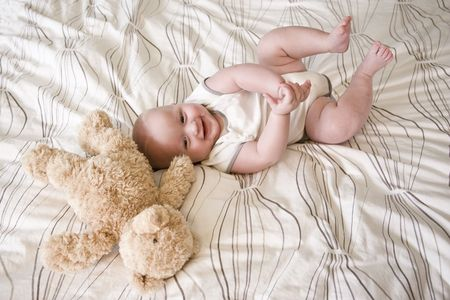 bedspread: Happy 7 month old baby lying down next to teddy bear