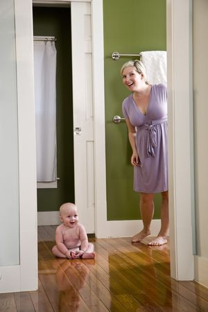 Mother standing beside happy 7 month old baby sitting on wood floor Stock Photo - 6610607