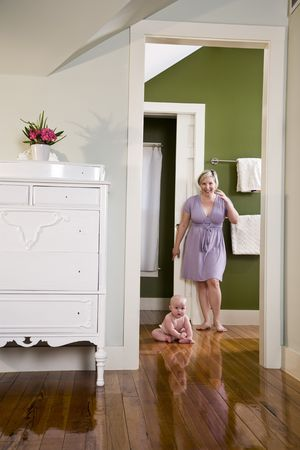 Mother standing beside chubby 7 month old baby sitting on wood floor photo