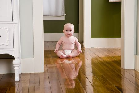 Chubby seven month old baby at home sitting on wood floor photo