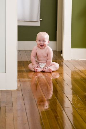 Amused 7 month old baby sitting on floor wearing diaper photo