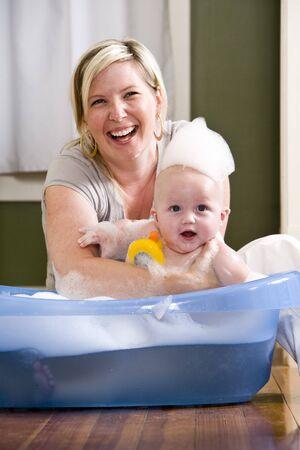 ba�arse: Feliz madre, su beb� de 7 meses de edad lindo de ba�o Foto de archivo