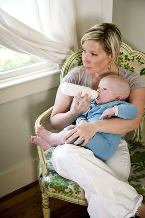 Mother bottle-feeding her seven month old baby Stock Photo - 6610695