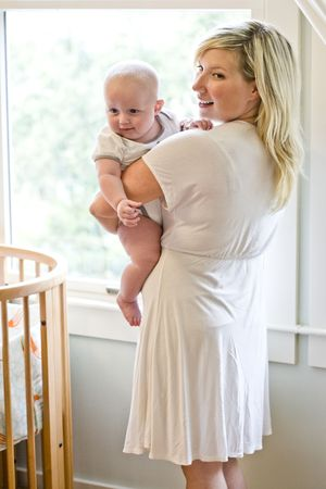 carrying: Mother carrying seven month old baby beside crib Stock Photo
