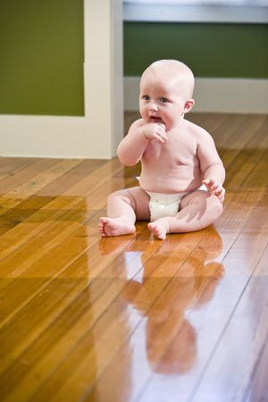 Chubby seven month old baby sitting on floor wearing diaper Stock Photo - 6610712