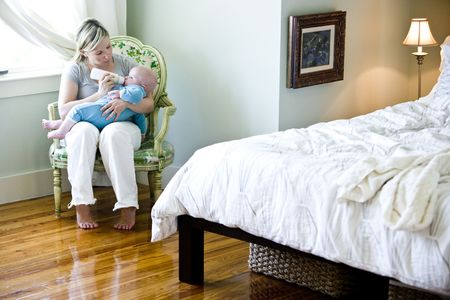 Mother feeding bottle to seven month old baby in bedroom Stock Photo - 6610705