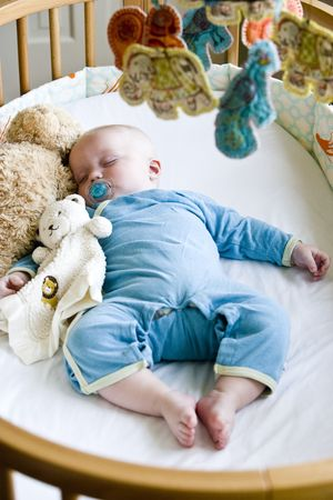 Seven month old baby boy sound asleep in his crib Stock Photo