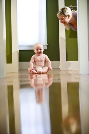 Cute seven month old chubby baby wearing diaper sitting on floor laughing at mother photo