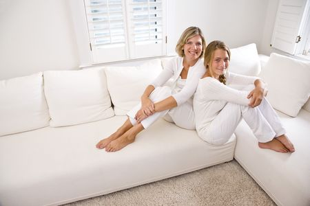 white sofa: Mother and teenage daughter relaxing at home in white living room