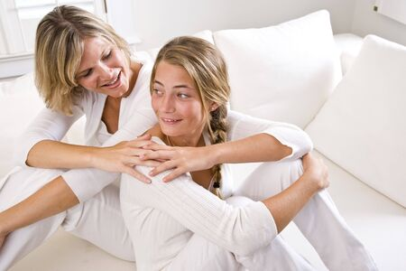 Mother and teenage daughter relaxing at home in white living room Stock Photo - 6610590