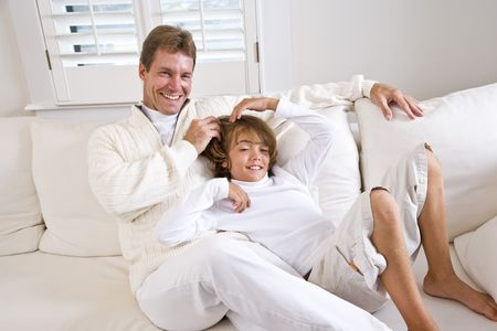 Father and son relaxing at home on white living room sofa