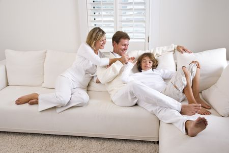 white sofa: Family relaxing at home on white living room sofa