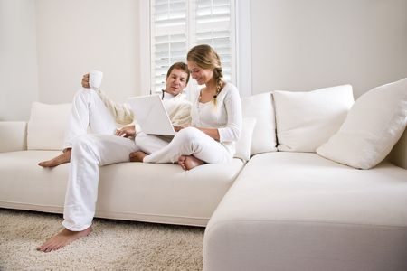 comfortable: Father and teenage daughter on white living room sofa using laptop