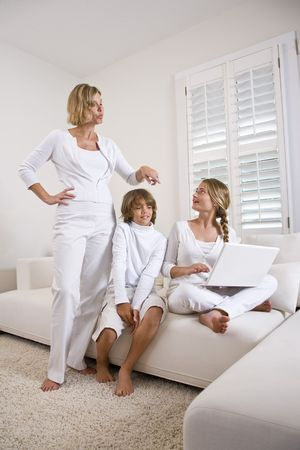 Mother and children on sofa using laptop photo