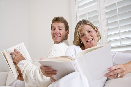 Couple relaxing together reading at home in white surroundings photo