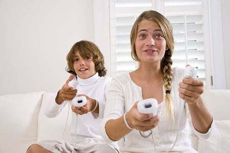 early teens: Brother and sister playing video game on white sofa